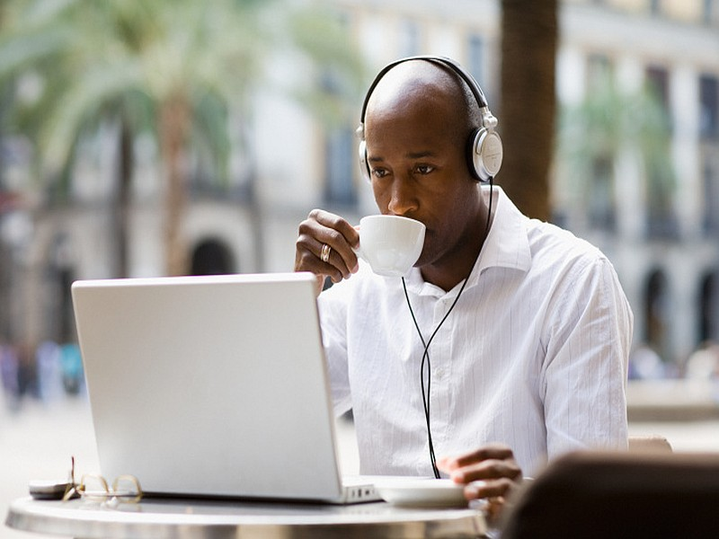 Man sitting at cafe table wearing headphones learning English