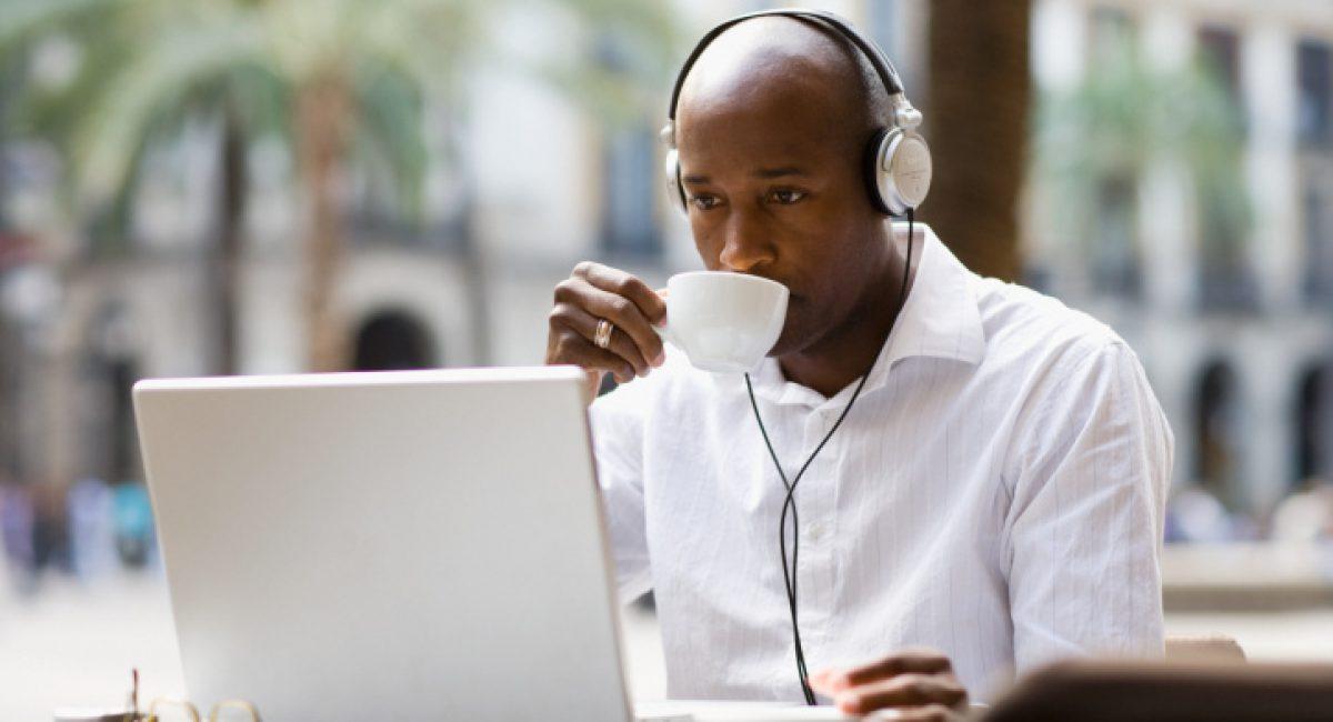 Man sitting at cafe table wearing headphones while using laptop